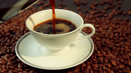 xícara de café : Pouring fresh hot coffee, white cup on beans background