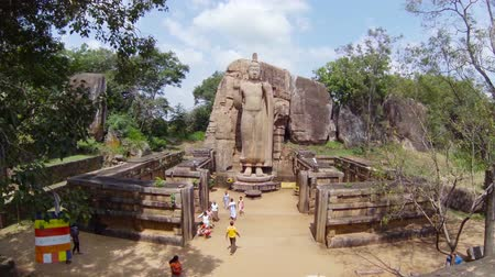 budha : KEKIRAWA, SRI LANKA - APR 16: Pilgrims pray near Avukana Buddha statue on Apr 16, 2013 in Avukana, Sri Lanka. It is 40 feet (12 m) high standing statue carved out of granite rock in the 5th century.