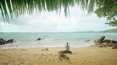 остров : Video 1920x1080 - A lone man sits on the shore of a tropical ocean