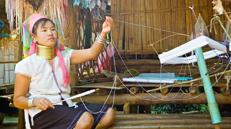 hill tribe : CHIAND RAI. THAILAND - 04 DEC 2013: One Kayan Lahwi (Long-Necked Kayan) woman with neck rings spin yarn in hill tribe village. Stock Footage