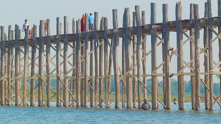 mianmar : MANDALAY. MYANMAR - 13 JAN 2014: U Bein Bridge across the Taungthaman Lake. The 1.2 km  bridge was built around 1850 and is the oldest and longest teakwood bridge in the world Stock mozgókép