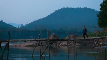 kırsal : LUANG PRABANG. LAOS - 08 DEC 2013: Unidentified men pass long wooden bridge above river at dark evening