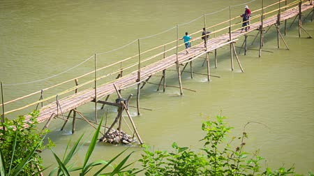 prabang : LUANG PRABANG. LAOS - 08 DEC 2013: Unidentified people pass long wooden bridge above river