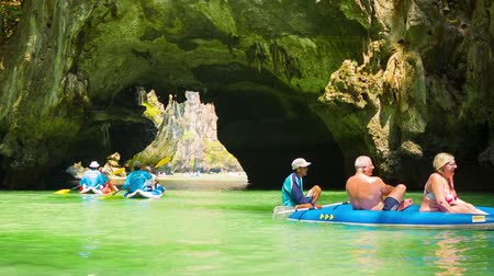 exotikou : PHANG NGA. THAILAND - 24 FEB 2014: Tourists kayaking among limestone cliffs. Phuket Island and other islands of Thailand popular with tourists