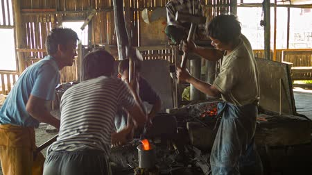 kowal : INLE LAKE. MYANMAR - CIRCA JAN 2014: Burmese blacksmiths work in the forge. Manufacture of weapons - traditional way.