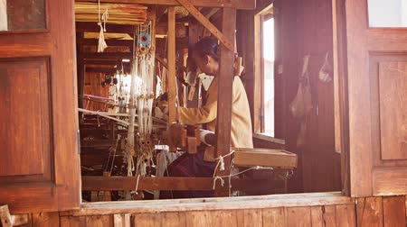 kumaş : INLE LAKE. MYANMAR - CIRCA JAN 2014: Old weaving factory. A local woman has been producing of fabric on a loom Stok Video