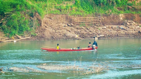 prabang : LUANG PRABANG. LAOS - CIRCA DEC 2013: Family locals is pulling a boat against the tide Stock Footage