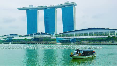 baía : SINGAPORE - 01 JAN 2014: Boat with tourists cross marina Bay with Marina Bays Sands building on background
