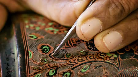 lacquerware : BAGAN. MYANMAR - 10 JAN 2014: Etching with needle close up stage in traditional Burmese lacquerware handmade. Yun-de is lacquerware in Burmese. and the art is called Pan yun. Stock Footage
