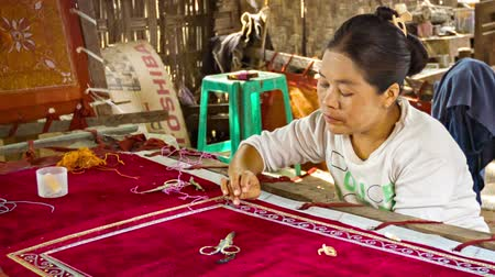 Бирма : MANDALAY. MYANMAR - 13 JAN 2014: Burmese tapestry masters work with kalaga. It is a heavily embroidered applique tapestry made of silk. flannel. felt. wool and lace against cotton or velvet background