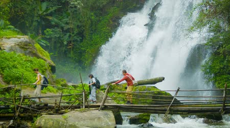 hátizsákkal : Video 1080p - Tourists cross the river on a background of a waterfall. Doi Inthanon National park. Thailand