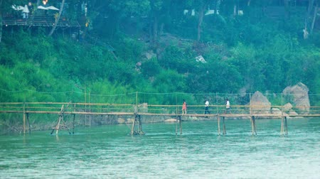 prabang : Video 1080p - People cross the river with the help of a bamboo footbridge. Luang Prabang. Laos Stock Footage