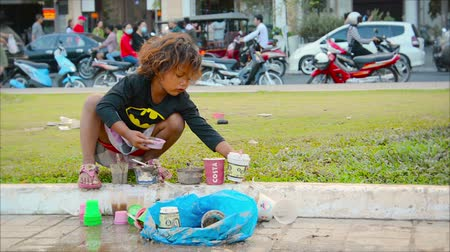 PHNOM PENH. CAMBODIA - 29 DEC 2013: A child plays on the sidewalk. against road traffic