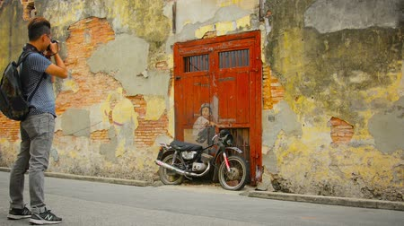 georgetown : GEORGE TOWN. PENANG. MALAYSIA - 22 JUL 2014: Boy on a Bike - wall painting and a tourist with a camera