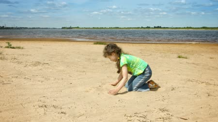 um : Video 1080p - Little girl playing with sand on the shore of a large river