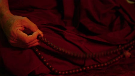 modlitba : Video 1080p - Rosary in hand of the monk meditating in a dark room (high level of digital noise)
