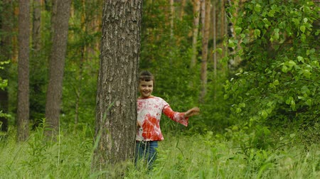 gizleme : UltraHD video - Happy child hiding behind a tree in the forest Stok Video