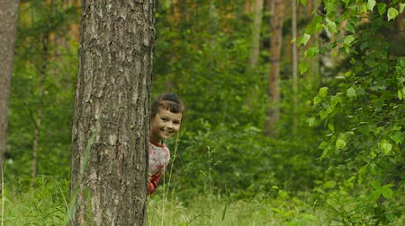 скрывать : Cheerful little girl hiding behind a tree in the forest