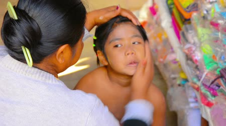 капелька : BAGAN. MYANMAR - CIRCA JAN 2014: Mother applies sunscreen thanaka on her daughters skin Стоковые видеозаписи