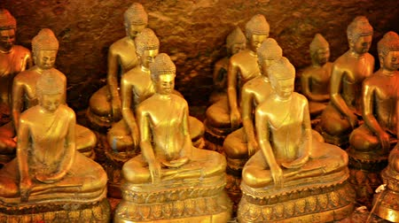 budista : Video 1080p - Panning from left to right across a collection of near-identical Buddhist statues in a village in Cambodia. Sculptures are gold-colored. and appear to be arranged in a cave Stock Footage