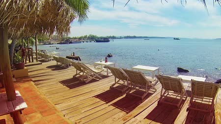 deck chairs : Overlooking a tropical beach in Sihanoukville at an oblique angle. A panoramic view of the horizon under sunny skies. Stock Footage