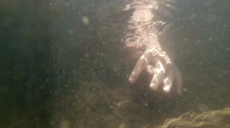 plunging : Video 1080p - Mans hand. recorded from a submarine perspective. plunging into the cool. clear water of a Thai mountain stream.