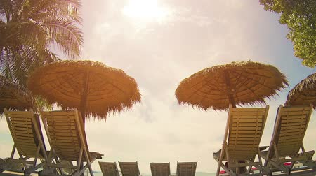 стулья : Pairs of beach chairs and umbrellas. made of natural fibers. arranged in the tropical sun at a resourt in Sihanoukville. Cambodia Стоковые видеозаписи