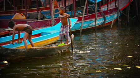 improvised : TONLE SAP LAKE. CAMBODIA - CIRCA DEC 2013: Two young Cambodian children balance precariously. standing in a small. handmade. wooden canoe in front of the village on stilts where they live. Stock Footage