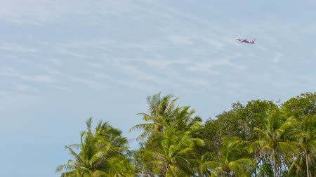 взятие : PHUKET. THAILAND - CIRCA NOV 2014: Red commercial jetplane flying over tall treetops in Thailand. Asia. Overcast sky in the background.