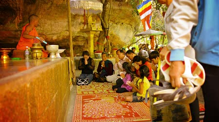 szerzetes : PHNOM KULEN. CAMBODIA - CIRCA DEC 2013: Whole family a Buddhist religious ceremony in Cambodia. Old and young can be seen sitting and praying as a monk presides over the ceremony.