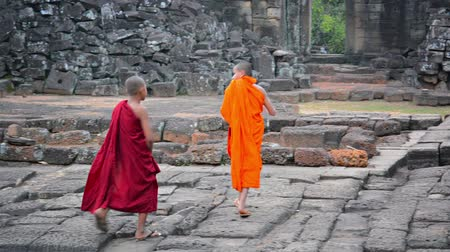 азиаты : SIEM REAP. CAMBODIA - CIRCA DEC 2013: Two boys in traditional monk robes running and playing on the stone steps at Bayon Temple in Siem Reap. Cambodia. Стоковые видеозаписи