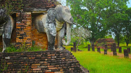 gerçeküstü : UHD video - Surreal. timelapse tracking shot of elephant sculptures surrounding an ancient Buddhist temple ruin in Southeast Asia. Stok Video