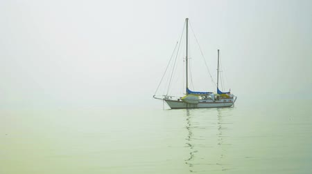 bermudas : Video FullHD - A beautiful. Bermuda-rigged sailboat rides peacefully at anchor in a lightly foggy harbor. Vídeos