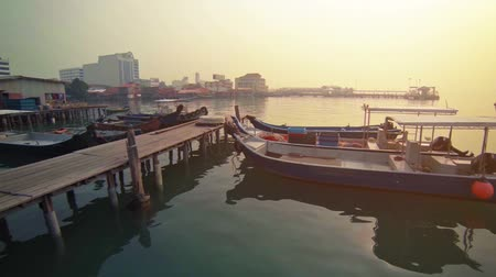 georgetown : Video 1920x1080 - Colorfully painted. handmade. wooden boats bob peacefully in the calm waters of this harbor while moored to a pier in Penang. Malaysia. Stock Footage
