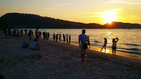 speedboats : PATONG. PHUKET. THAILAND - CIRCA JAN 2015: Beachgoers enjoying the sand and sea at Patong Beach as the sun sets over the horizon.