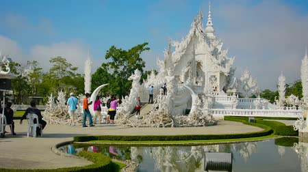 аккуратный : CHIANG RAI. THAILAND - CIRCA DEC 2013: A gardener trims the hedges in the foreground as tourists stroll into the White Temple. a popular tourist attraction in Chiang Rai. Thailand. Стоковые видеозаписи