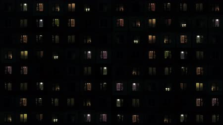 oŚwietlenie : UltraHD video - Backlighting from interior lighting is the only light in this night shot of a large apartment complex in Southeast Asia. with silhouettes of people in the windows.