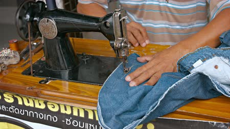 lem : BANGKOK. THAILAND - CIRCA FEB 2015: Local Worker Altering Jeans on an Old Sewing Machine in Bangkok. Thailand Dostupné videozáznamy
