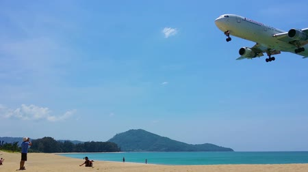 final destination : PHUKET. THAILAND - CIRCA FEB 2015: Tourist snaps a photo as an airliner buzzes the beach at low altitude. on final approach for landing at Phuket International Airport. in Thailand.