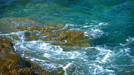 kullancs : Video UltraHD 3840x2160 - Warm tropical waters of the Anaman Sea. lapping gently at an enormnous. algae and barnacle-encrusted rock on the coast of Thailand.