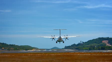 final destination : Video 1920x1080 - Small. turbo-prop commuter airplane lands at Phuket International Airport on a beautiful. sunny day. with a load of happy tourists.