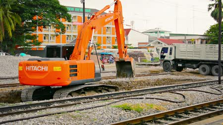 levelling : LOPBURI. THAILAND - CIRCA NOV 2013: Hydraulic excavator raking and levelling gravel at Lopburi Railway Station in Thailand. with sound.