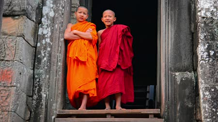 budist : SIEM REAP. CAMBODIA - CIRCA DEC 2013: Young. Buddhist monks. standing in an ancient doorway at Bayon Temple in Cambodia. Stok Video