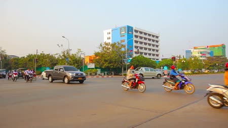 vientiane : VIENTIANE. LAOS - CIRCA DEC 2013: Light morning traffic at a typical urban intersection in Vientiane. Laos. on a clear. sunny day. Stock Footage