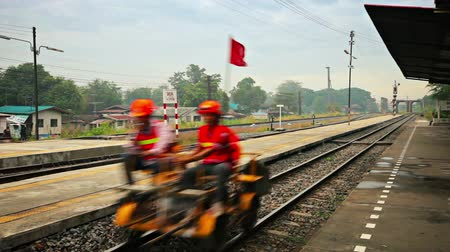 редакционный : BANG PAIN. THAILAND  CIRCA NOV 2013: Maintenance personnel cruise by the platform on a gaspowered drasine en route to a rail line repair job.