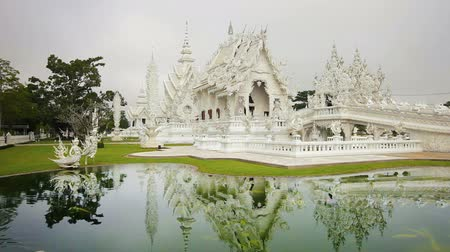 запутанный : CHIANG RAI. THAILAND  CIRCA DEC 2013: Fish in a pond and tourists strolling around at the white temple in Chiang Rai. Thailand. in timelapse.