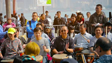 наслаждаться : HONG KONG. CHINA - CIRCA JAN 2015: Tourists beating out rhythms on percussian instruments at the terminal as passengers wait for the next ferry in the background. Стоковые видеозаписи