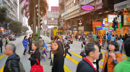 kerület : HONG KONG. CHINA - CIRCA JAN 2015: Swarm of pedestrians crossing a major city street in the downtown business district of Hong Kong.