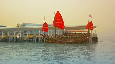Виктория : HONG KONG. CHINA - CIRCA JAN 2015:  Tour boat. patterned after an old fashioned Chinese sailing junk. arriving to take on passengers in Victoria Harbor. Hong Kong. Стоковые видеозаписи