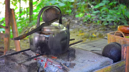 boletim informativo : Video 1080p - Old tea kettle. blackened with soot. heats over the red hot coals of an outdoor cooking fire on the island of Borneo in Southeast Asia.